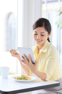 タブレットを見ながら朝食を食べる女性の写真素材 [FYI02030793]