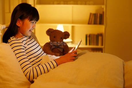 ベッドでタブレットを操作する女の子の写真素材 [FYI02030796]