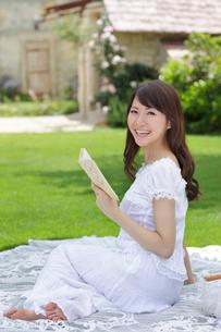 芝生で読書をする若い女性の写真素材 [FYI02030799]