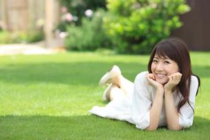 芝生で寝転ぶ若い女性の写真素材 [FYI02030800]