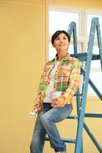 建築現場でペンキ缶を持ち室内を眺める女性の写真素材 [FYI02030802]