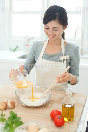 明るいキッチンで料理する女性の写真素材 [FYI02030808]
