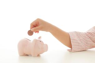 貯金箱にお金を入れる子どもの手の写真素材 [FYI02030821]