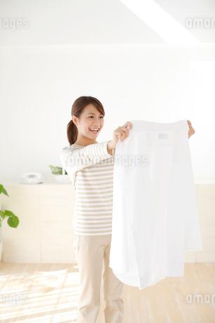 ワイシャツを広げる若い女性の写真素材 [FYI02030833]