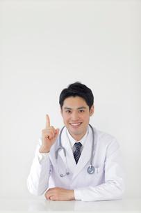 優しい笑顔で指差しポーズをする医師の写真素材 [FYI02030857]