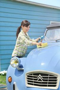 水色の可愛い自動車を洗車する女性の写真素材 [FYI02030870]