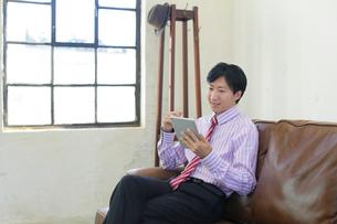ソファーで寛ぎながら仕事をするビジネスマンの写真素材 [FYI02030904]
