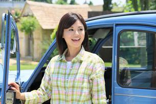水色の可愛い車から降りる若い女性の写真素材 [FYI02030911]