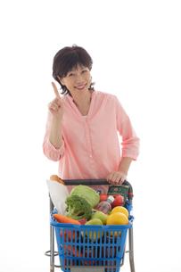 ショッピングカートを押しながら買い物をするシニアの女性の写真素材 [FYI02030912]