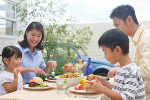庭でランチを楽しむ家族の写真素材 [FYI02030949]