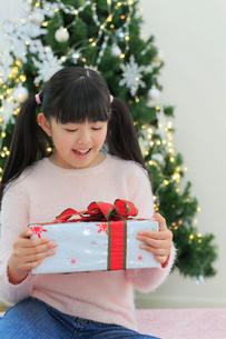 クリスマスツリーのある部屋でくつろぐ女の子の写真素材 [FYI02030953]
