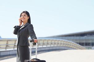 スーツケースを持ち携帯で話をするビジネスウーマンの写真素材 [FYI02030976]