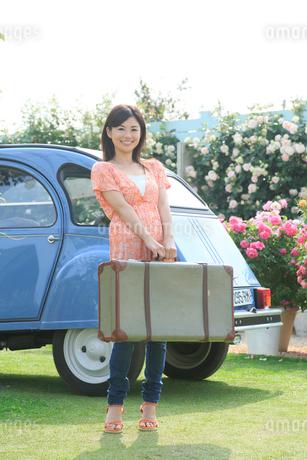 水色の可愛い車とスーツケースと若い女性の写真素材 [FYI02030985]
