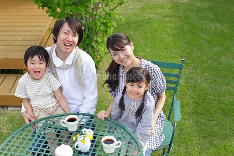 庭のテーブルでお茶を楽しむ4人家族の写真素材 [FYI02031006]