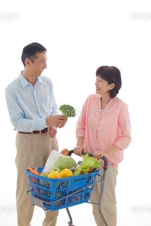 ショッピングカートを押しながら買い物をするシニアの夫婦の写真素材 [FYI02031012]