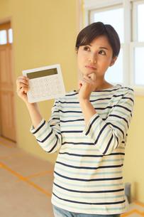 計算機を手に建築費用に悩む女性の写真素材 [FYI02031020]
