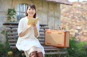 トランクを持ちベンチに座る若い女性の写真素材 [FYI02031060]
