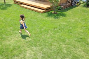 芝生の庭を走る女の子の写真素材 [FYI02031097]