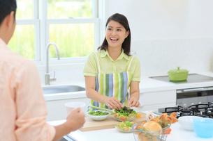 明るいキッチンで料理をする妻とお茶を飲む夫の写真素材 [FYI02031132]