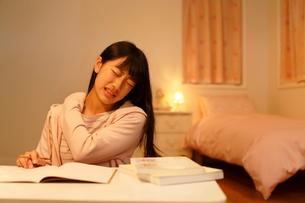 深夜の勉強中に肩こりに苦しむ女の子の写真素材 [FYI02031135]