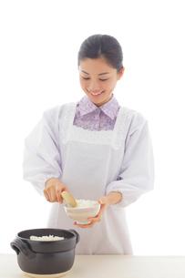 ご飯をお茶碗によそう割烹着のお母さんの写真素材 [FYI02031144]