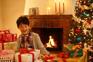 クリスマスツリーとプレゼントに囲まれたと男の子の写真素材 [FYI02031195]