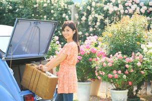 水色の可愛い車とスーツケースと若い女性の写真素材 [FYI02031200]