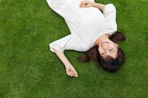 芝生で寝転ぶ若い女性の写真素材 [FYI02031202]