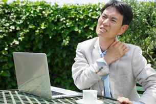 肩こりに顔をゆがめる中年男性の写真素材 [FYI02031205]
