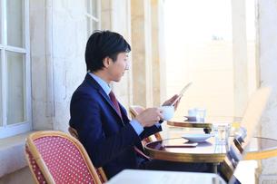 カフェで仕事をするビジネスマンの写真素材 [FYI02031236]