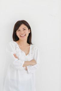 白い壁の前で腕を組み笑う女性の写真素材 [FYI02031246]