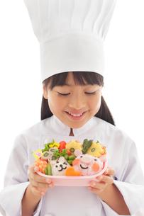 お弁当を見せる女の子のシェフの写真素材 [FYI02031248]