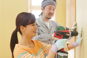 大工さんに作業を習う女性の写真素材 [FYI02031251]