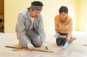 床材を貼る大工の男性と習う女性の写真素材 [FYI02031262]