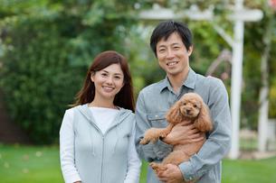 庭で寄り添う夫婦と犬の写真素材 [FYI02031265]