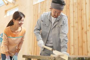 大工さんに作業を習う女性の写真素材 [FYI02031281]