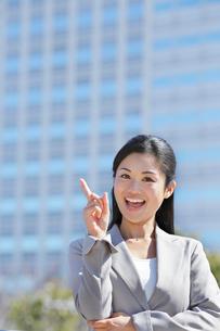 ビル街で指さしポーズをするビジネスウーマンの写真素材 [FYI02031287]