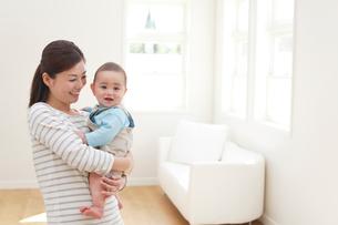 リビングでお母さんに抱っこされる赤ちゃんの写真素材 [FYI02031297]