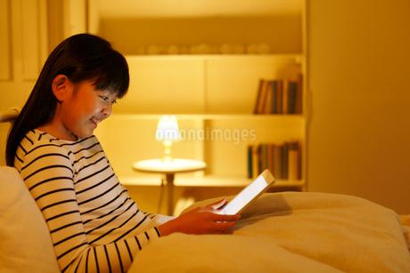 ベッドでタブレットを操作する女の子の写真素材 [FYI02031304]