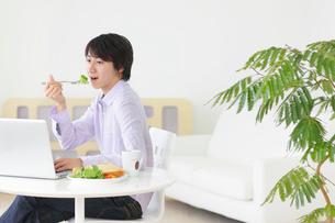 朝食を食べながらホームオフィスで仕事をする若い男性の写真素材 [FYI02031312]