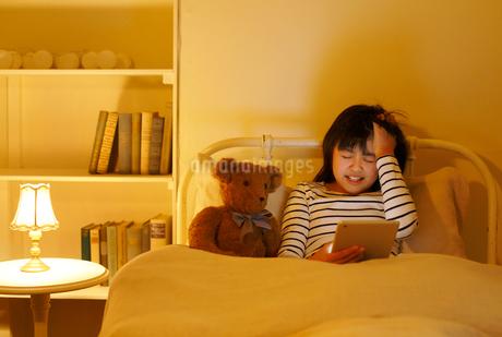 ベッドでタブレットを操作する女の子の写真素材 [FYI02031328]