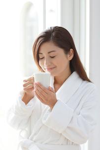 入浴後に窓辺でコーヒーを楽しむ女性の写真素材 [FYI02031334]