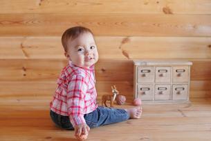 木の床に座って遊ぶ赤ちゃんの写真素材 [FYI02031342]