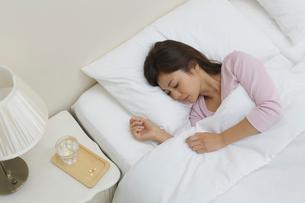 体調不良で寝る女性とテーブルに置かれた薬の写真素材 [FYI02031354]