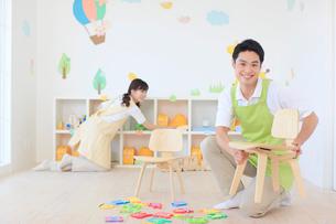 教室の片づけをする男女の幼稚園の先生の写真素材 [FYI02031359]