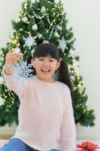 クリスマスツリーのある部屋でくつろぐ女の子の写真素材 [FYI02031387]