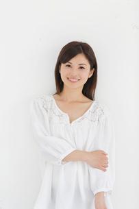 白い壁の前で笑う女性の写真素材 [FYI02031393]