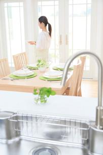 ダイニングキッチンでテーブルセッティングをする女性の写真素材 [FYI02031394]