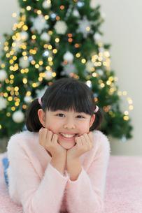 クリスマスツリーのある部屋でくつろぐ女の子の写真素材 [FYI02031401]