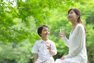 新緑の中で水を飲むお母さんと男の子の写真素材 [FYI02031419]